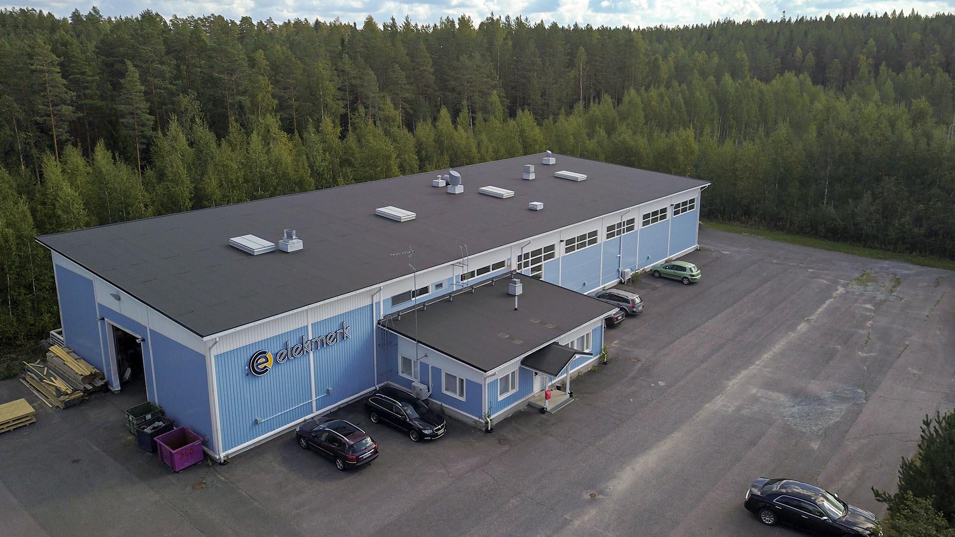 Ilmakuva tehdashallista. Pihassa on autoja ja taustalla metsää.