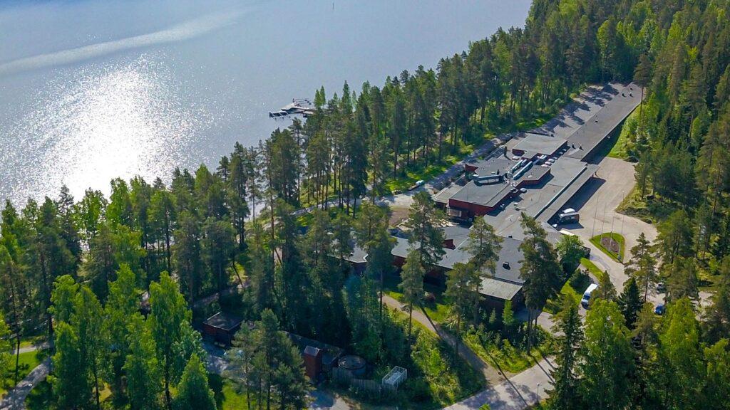 Ilmakuva hotellista. Hotellin parkkipaikalla on autoja. Ympärillä on metsää ja järvi.