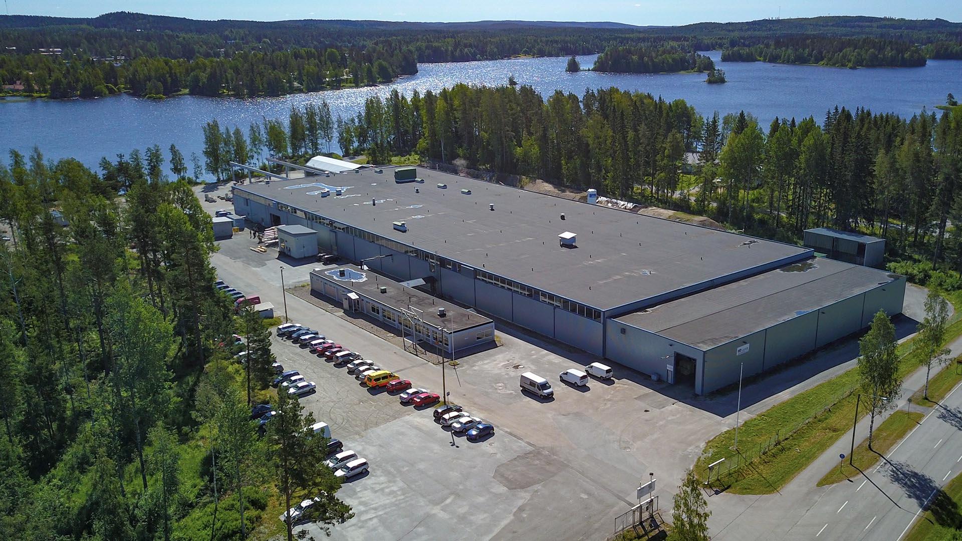 Ilmakuva tehdashallista. Pihassa on autoja ja ympärillä metsää sekä järvi.
