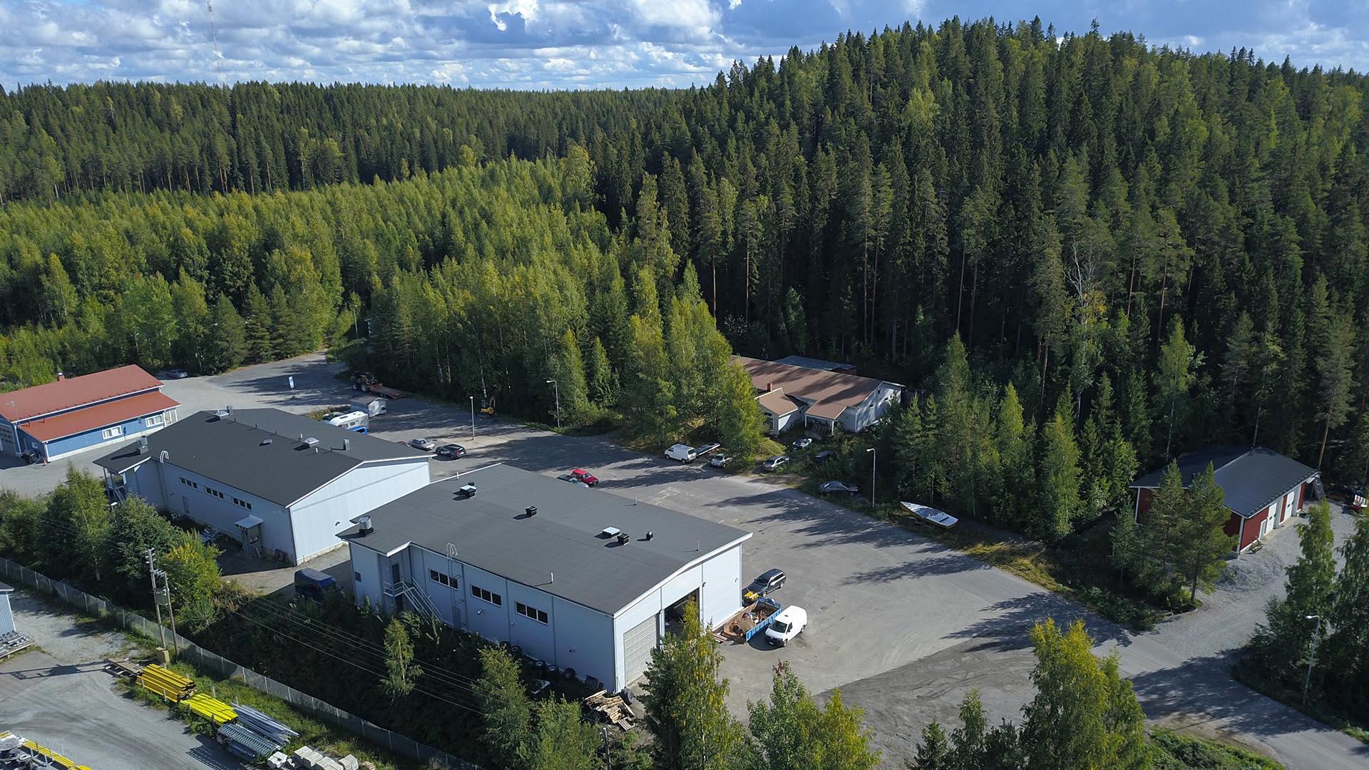 Ilmakuva tehdashallista. Pihassa on autoja ja ympärillä metsää.