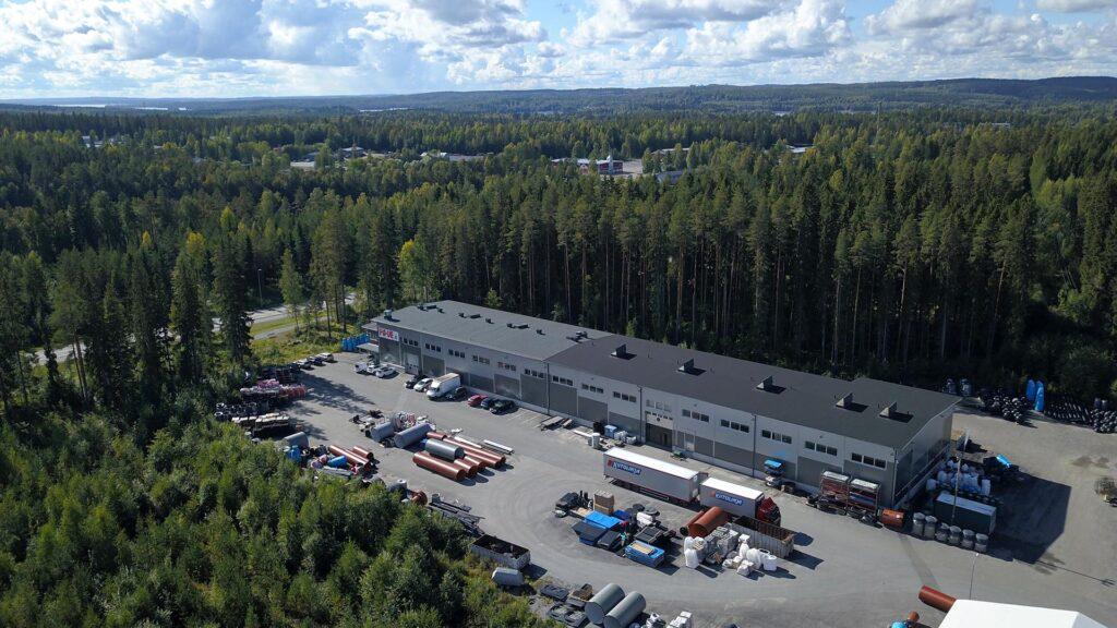 Ilmakuva tehdashallista. Ympärillä on metsää.